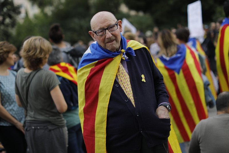 An elderly man joins a pro-independence gathering outside the Sagrada Família basilica i on the fifth day of protests over the conviction of a dozen Catalan independence leaders in Barcelona, Spain, Friday, Oct. 18, 2019. Various flights into and out of the region are cancelled Friday due to a general strike called by pro-independence unions and five marches of tens of thousands from inland towns are expected converge in Barcelona's center on Friday afternoon for a mass protest with students to and workers who are on strike. (AP Photo/Bernat Armangue)