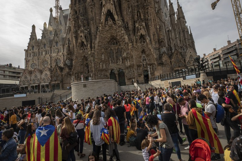 Demonstrators join a pro-independence gathering outside the Sagrada Família basilica during the fifth day of protests over the conviction of a dozen Catalan independence leaders in Barcelona, Spain, Friday, Oct. 18, 2019. Various flights into and out of the region are cancelled Friday due to a general strike called by pro-independence unions and five marches of tens of thousands from inland towns are expected converge in Barcelona's center on Friday afternoon for a mass protest with students to and workers who are on strike. (AP Photo/Bernat Armangue)
