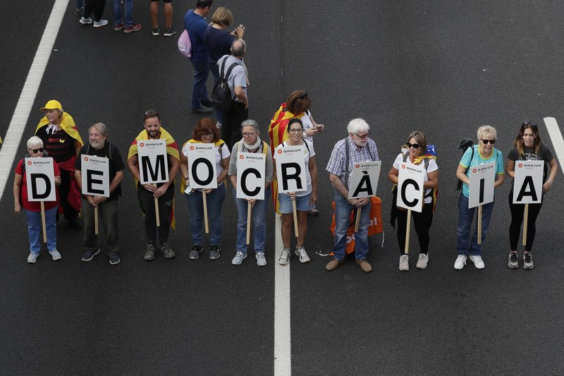 Protesters march with a letters reading 'Democracy' on the fifth day of protests over the conviction of a dozen Catalan independence leaders in Barcelona, Spain, Friday, Oct. 18, 2019. Various flights into and out of the region are cancelled Friday due to a general strike called by pro-independence unions and five marches of tens of thousands from inland towns are expected converge in Barcelona's center on Friday afternoon for a mass protest with students to and workers who are on strike. (AP Photo/Manu Fernandez)