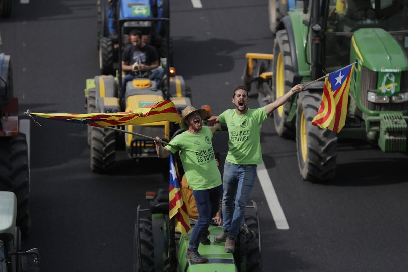 Protesters ride on tractors as they enter the city on the fifth day of protests over the conviction of a dozen Catalan independence leaders in Barcelona, Spain, Friday, Oct. 18, 2019. Various flights into and out of the region are cancelled Friday due to a general strike called by pro-independence unions and five marches of tens of thousands from inland towns are expected converge in Barcelona's center on Friday afternoon for a mass protest with students to and workers who are on strike. (AP Photo/Manu Fernandez)