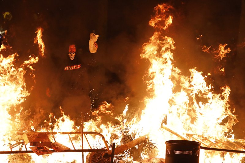A protestors pours gasoline on a burning barricade during clashes with police in Barcelona, Spain, Thursday, Oct. 17, 2019. Catalonia's separatist leader vowed Thursday to hold a new vote to secede from Spain in less than two years as the embattled northeastern region grapples with a wave of violence that has tarnished a movement proud of its peaceful activism. (AP Photo/Emilio Morenatti)