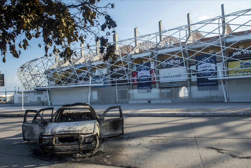 A burnt out vehicle used by gunmen sits abandoned next to a stadium, a day after street battles between gunmen and security forces in Culiacan, Mexico, Friday Oct. 18, 2019. Mexican security forces backed off an attempt to capture a son of imprisoned drug lord Joaquin