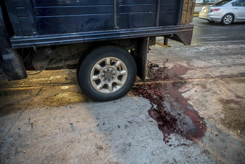 """Blood stains the street after a gunfight in Culiacan, Mexico, Thursday, Oct. 17, 2019. An intense gunfight with heavy weapons and burning vehicles blocking roads raged in the capital of Mexico's Sinaloa state Thursday after security forces located one of Joaquín """"El Chapo"""" Guzmán's sons who is wanted in the U.S. on drug trafficking charges. (AP Photo/Augusto Zurita)"""