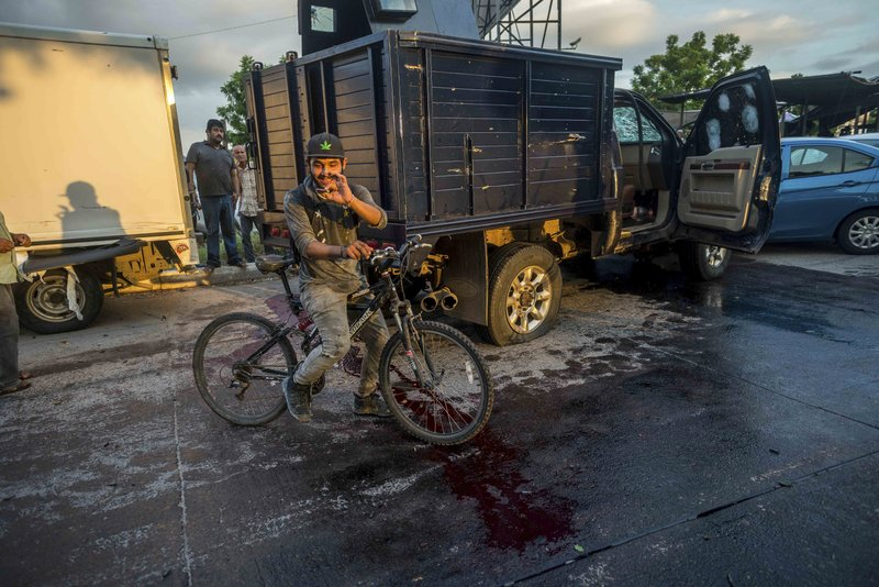 """A man handles a bullet cartridge in a blooded street by a truck with a flat tire and covered with bullet hits after a gunfight in Culiacan, Mexico, Thursday, Oct. 17, 2019. An intense gunfight with heavy weapons and burning vehicles blocking roads raged in the capital of Mexico's Sinaloa state Thursday after security forces located one of Joaquín """"El Chapo"""" Guzmán's sons who is wanted in the U.S. on drug trafficking charges. (AP Photo/Augusto Zurita)"""