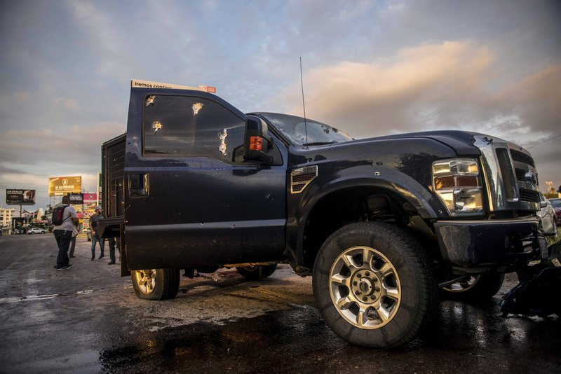 """A truck's windows shows hits from bullets after a gunfight in Culiacan, Mexico, Thursday, Oct. 17, 2019. An intense gunfight with heavy weapons and burning vehicles blocking roads raged in the capital of Mexico's Sinaloa state Thursday after security forces located one of Joaquín """"El Chapo"""" Guzmán's sons who is wanted in the U.S. on drug trafficking charges. (AP Photo/Hector Parra)"""