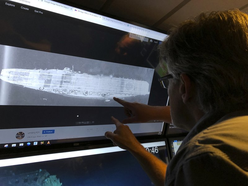 In this Wednesday, Oct. 16, 2019, photo, Vulcan Inc. director of subsea operations of the Petrel, Rob Kraft looks at images of the Japanese aircraft carrier Kaga, off Midway Atoll in the Northwestern Hawaiian Islands. Deep-sea explorers scouring the world's oceans for sunken World War II ships are honing in on a debris field deep in the Pacific. The research vessel called the Petrel is launching underwater robots about halfway between the U.S. and Japan in search of warships from the Battle of Midway. (AP Photo/Caleb Jones)