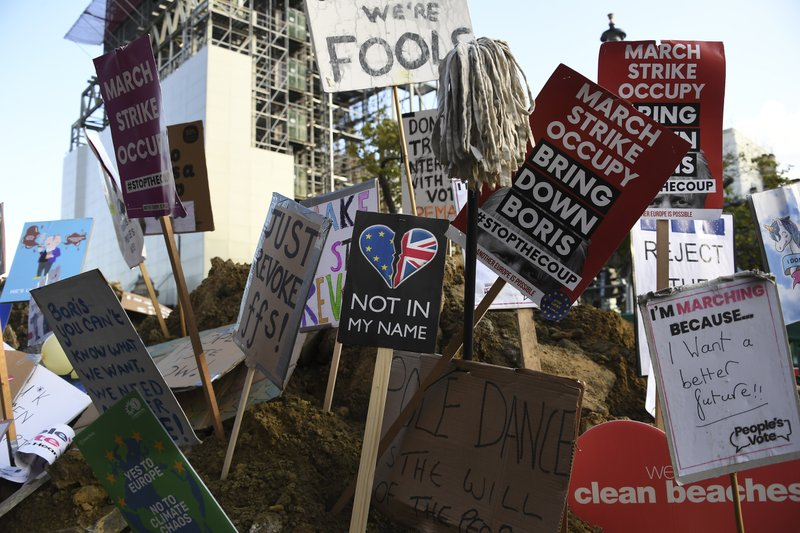 Anti-Brexit signs are left in a pile of earth after a protest gathering in London, Saturday, Oct. 19, 2019. In a major blow to British Prime Minister Boris Johnson, U.K. lawmakers voted Saturday to postpone a decision on whether to back his Brexit deal with the European Union, throwing a wrench into government plans to leave the bloc at the end of this month. (AP Photo/Alberto Pezzali)