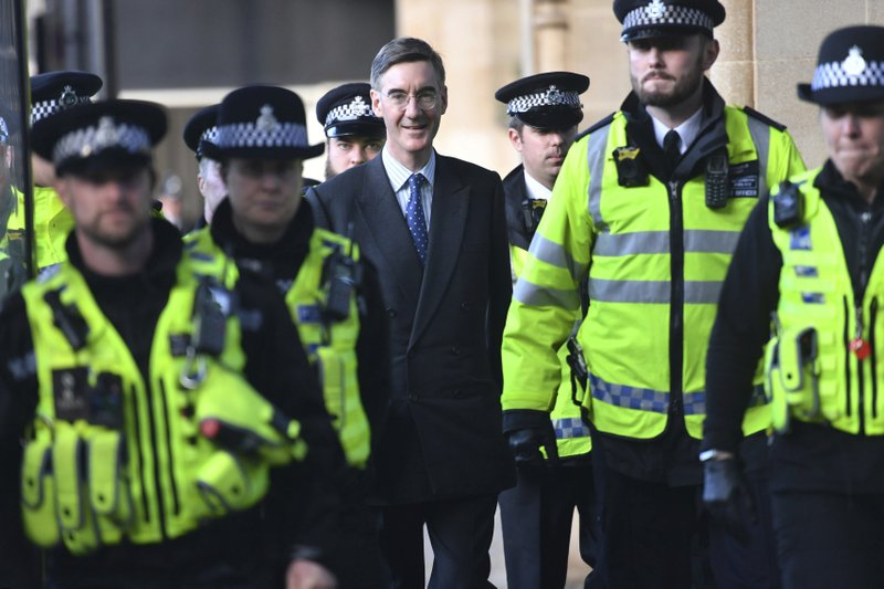 A heavy police presence escorts Leader of Britain's House of Commons Jacob Rees-Mogg from parliament in London, following a Brexit debate Saturday Oct. 19, 2019.  Many thousands of protesters gathered in London to demonstrate on both sides of the Brexit argument.  (Jacob King/PA via AP)