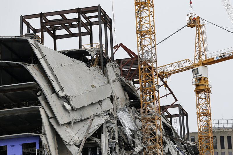 Workers begin the process of preparing the two unstable cranes for implosion at the collapse site of the Hard Rock Hotel, which underwent a partial, major collapse while under construction last Sat., Oct., 12, in New Orleans, Friday, Oct. 18, 2019.  Plans have been pushed back a day to bring down two giant, unstable construction cranes in a series of controlled explosions before they can topple onto historic New Orleans buildings, the city's fire chief said Friday, noting the risky work involved in placing explosive on the towers. (AP Photo/Gerald Herbert)