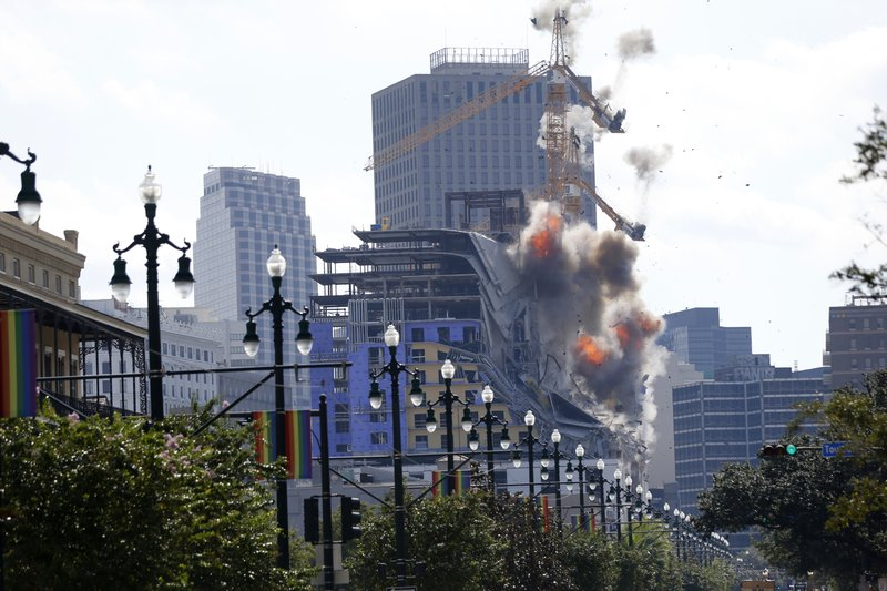 Two large cranes from the Hard Rock Hotel construction collapse come crashing down after being detonated for implosion in New Orleans, Sunday, Oct. 20, 2019. New Orleans officials set off several explosions Sunday intended to topple two cranes that had been looming precariously over the ruins of a partially collapsed hotel, but only one crane appeared to make it to the ground. (AP Photo/Gerald Herbert)
