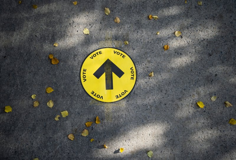 A sign directing voters to a polling station is taped to the sidewalk among autumn leaves, on election day of the 2019 federal election, in Ottawa, Ontario, Monday, Oct. 21, 2019. (Justin Tang/The Canadian Press via AP)