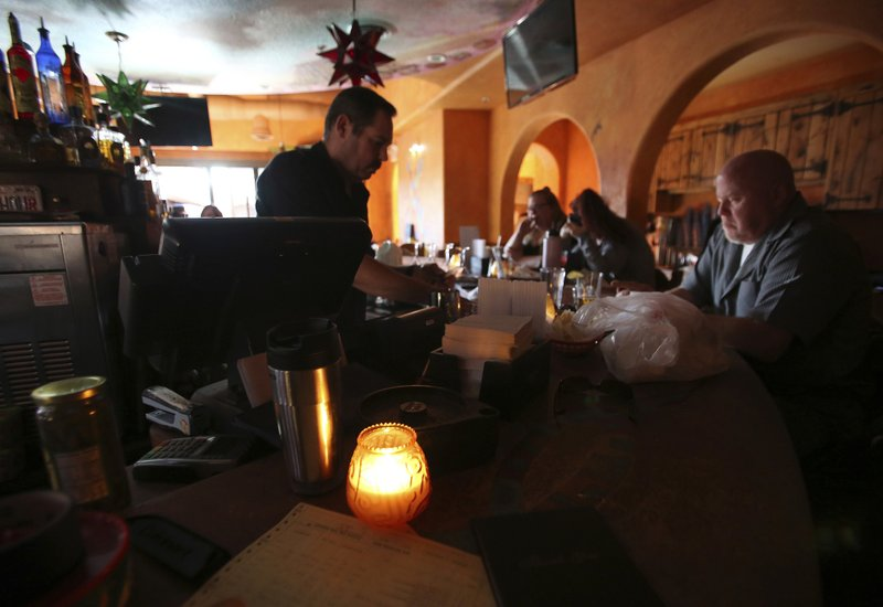 Maria's restaurant staff work in candle light as they choose to stay open with a limited menu offering after losing power Wednesday evening, Oct. 23, 2019, in downtown Grass Valley, Calif. Lights went out across large portions of Northern California on Wednesday, as the state's largest utility began its second massive blackout in two weeks, citing the return of dangerous fire weather. (Elias Funez/The Union via AP)