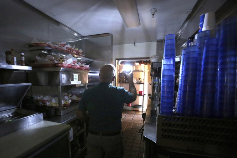 Maria's Restaurant manager Rich Fuxjager holds a battery powered lamp in the kitchen of Maria's restaurant as they continue to work with a limited menu following a power outage, Wednesday, Oct. 23, 2019, in Grass Valley, Calif. Lights went out across large portions of Northern California on Wednesday, as the state's largest utility began its second massive blackout in two weeks, citing the return of dangerous fire weather. (Elias Funez/The Union via AP)