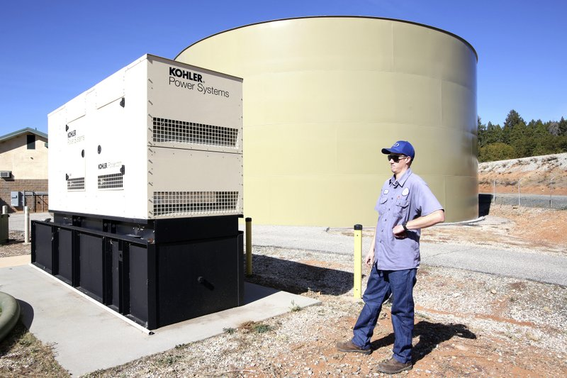 NID electrical systems technician Richard Dills stands next to a 300,000 watt industrial diesel powered generator used to keep treated water flowing to residents during the shutdown Wednesday, Oct. 23, 2019, in Grass Valley, Calif. Lights went out across large portions of Northern California on Wednesday, as the state's largest utility began its second massive blackout in two weeks, citing the return of dangerous fire weather. (Elias Funez/The Union via AP)