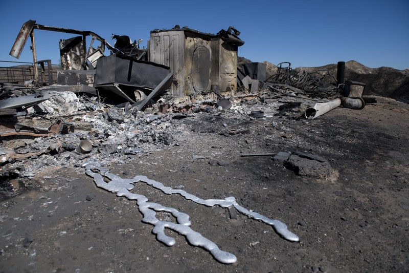 Debris from a hilltop home smolders after being burned by the Tick Fire, Thursday, Oct. 25, 2019, in Santa Clarita, Calif. An estimated 50,000 people were under evacuation orders in the Santa Clarita area north of Los Angeles as hot, dry Santa Ana winds howling at up to 50 mph (80 kph) drove the flames into neighborhoods (AP Photo/ Christian Monterrosa)