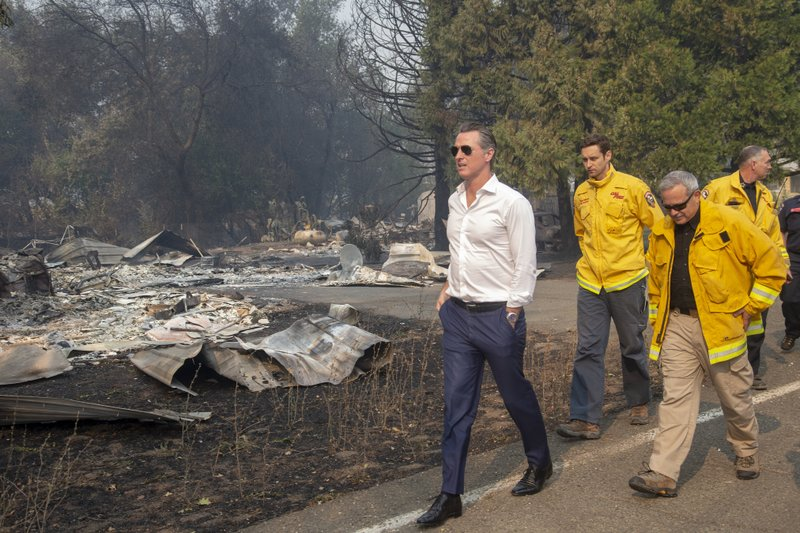 California Gov. Gavin Newsom, left, tours a home destroyed by the Kincade fire on Friday, Oct. 25, 2019, in Geyserville, Calif. Newsom declared a state of emergency Friday as wildfires scorch both ends of the state from Sonoma to Los Angeles. (Karl Mondon/San Jose Mercury News via AP)