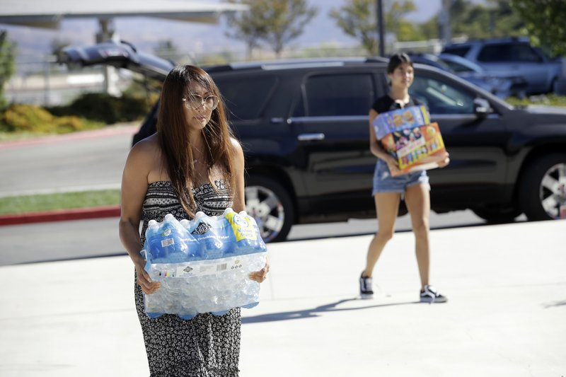 Christine Price, left, drops off food and water for evacuees from the Tick Fire with the help of her daughter Tinley, background right, at a shelter at West Ranch High School Friday, Oct. 25, 2019, in Santa Clarita, Calif. (AP Photo/Marcio Jose Sanchez)