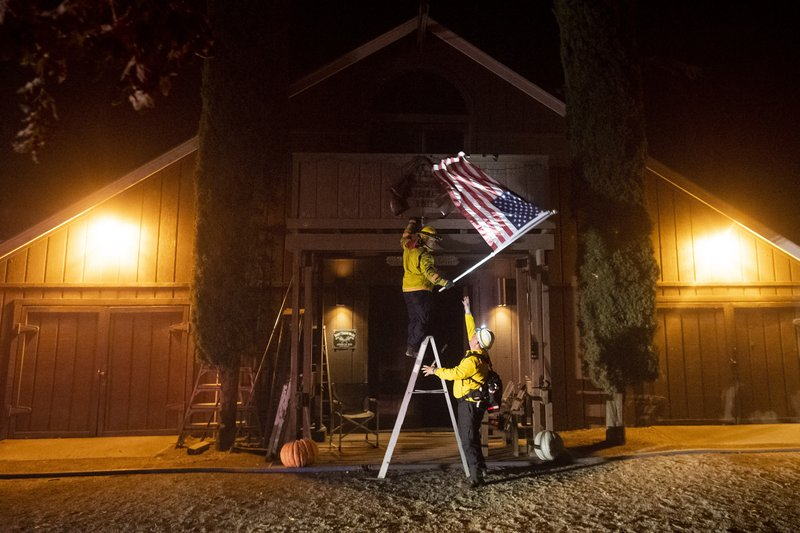 Firefighters from Dry Creek Rancheria remove an American flag as the Kincade Fire bears down on Healdsburg, Calif., on Sunday, Oct. 27, 2019. (AP Photo/Noah Berger)