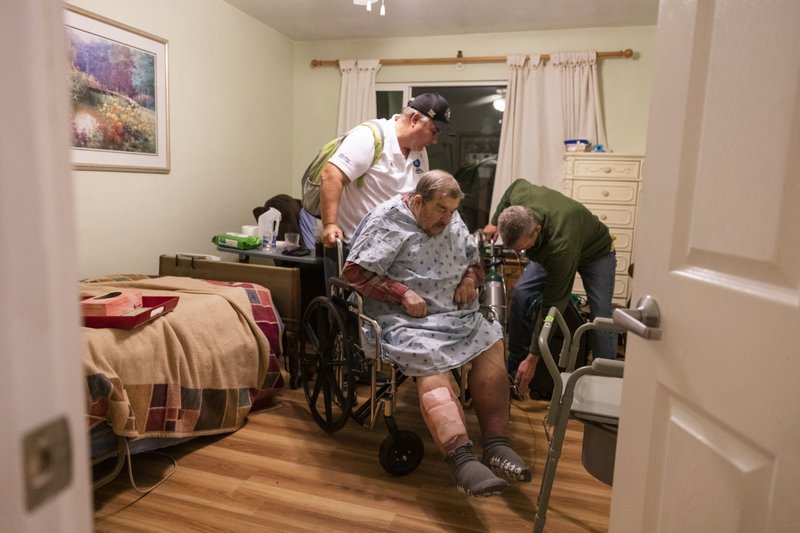 Henry Provencher, center, 87, receives help from his son Henry Provencher, left, and Eric Moessing, right, while evacuating Redwood Retreats, a residential care facility Santa Rosa, Calif., on Saturday, Oct. 26, 2019. A Northern California blaze forced evacuation orders and warnings for nearly all of Sonoma County stretching to the coast, with forecasts of strong winds prompting officials to start cutting electricity for millions of people in an effort to prevent more fires. (AP Photo/Ethan Swope)
