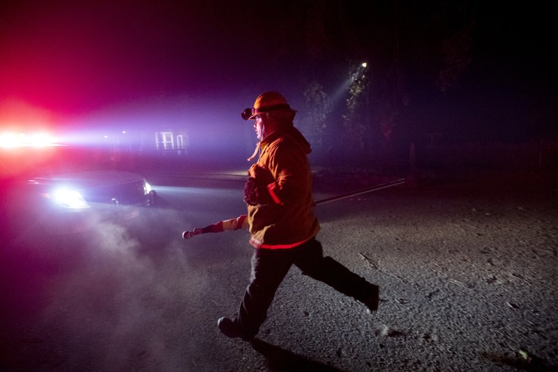 A firefighter from Dry Creek Rancheria carries a flag he removed from a building as the Kincade Fire bears down on Healdsburg, Calif., on Sunday, Oct. 27, 2019. (AP Photo/Noah Berger)
