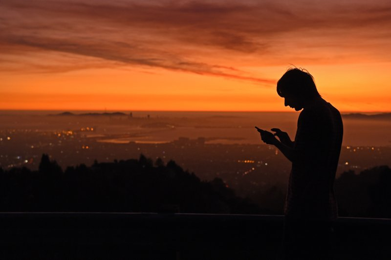 Kris Bel, of Concord, checks his smart phone as smoke lingers above the San Francisco skyline viewed from Grizzly Peak Blvd. in Oakland, Calif., Saturday, Oct. 26, 2019. Pacific Gas & Electric started shutting off power Saturday around 5 p.m. for an estimated 2.35 million people across 38 counties. (Jose Carlos Fajardo/East Bay Times via AP)