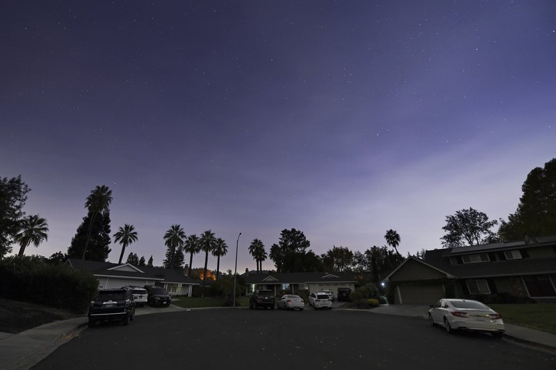 Stars can be seen in the sky as electricity in a neighborhood is turned off during a Pacific Gas & Electric  outage in Walnut Creek, Calif., on Saturday, Oct. 26, 2019. A Northern California blaze forced evacuation orders and warnings for nearly all of Sonoma County stretching to the coast, with forecasts of strong winds prompting officials to start cutting electricity for millions of people in an effort to prevent more fires. (Jose Carlos Fajardo/East Bay Times via AP)