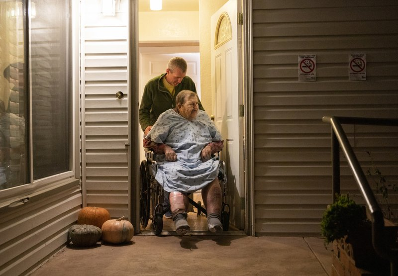 Henry Provencher, 87, is wheeled out of Redwood Retreats, a residential care facility by owner Eric Moessing while evacuating due to the Kincade Fire in Santa Rosa, Calif., on Saturday, Oct. 26, 2019. The evacuation order encompassed a huge swath of wine country stretching from the inland community of Healdsburg west through the Russian River Valley and to Bodega Bay on the coast, Sonoma County Sheriff Mark Essick said. (AP Photo/Ethan Swope)