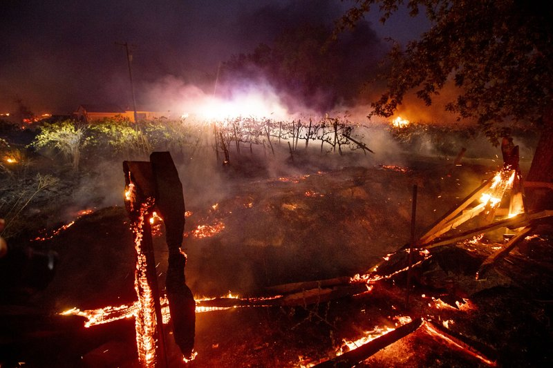A fence burns in front of a vineyard as the Kincade Fire burns in Healdsburg, Calif., on Sunday, Oct 27, 2019. (AP Photo/Noah Berger)