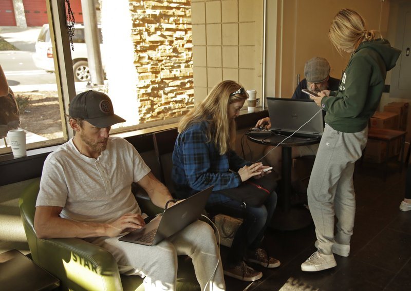 Customers charge their electronic devices at Starbuck's coffee shop on Monday, Oct. 28, 2019, in Lafayette, Calif. A large part of Lafayette has been without power. PG&E said Monday its power lines may have started two wildfires over the weekend in the San Francisco Bay Area despite widespread blackouts meant to prevent fires from igniting during dangerously windy weather. (AP Photo/Ben Margot)
