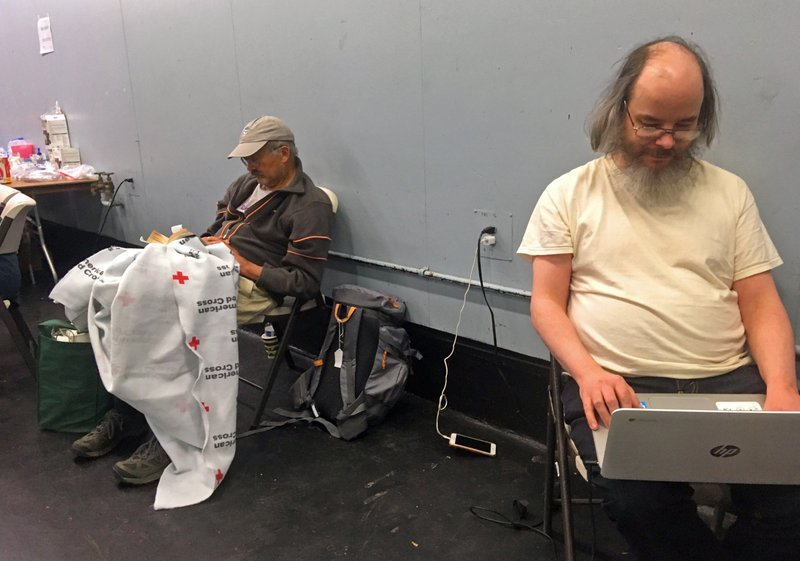 Chris Sherman of Santa Rosa, Calif., right, has his laptop computer plugged in so he can read at a Red Cross shelter in Santa Rosa Monday, Oct. 28, 2019. (AP Photo Don Thompson)