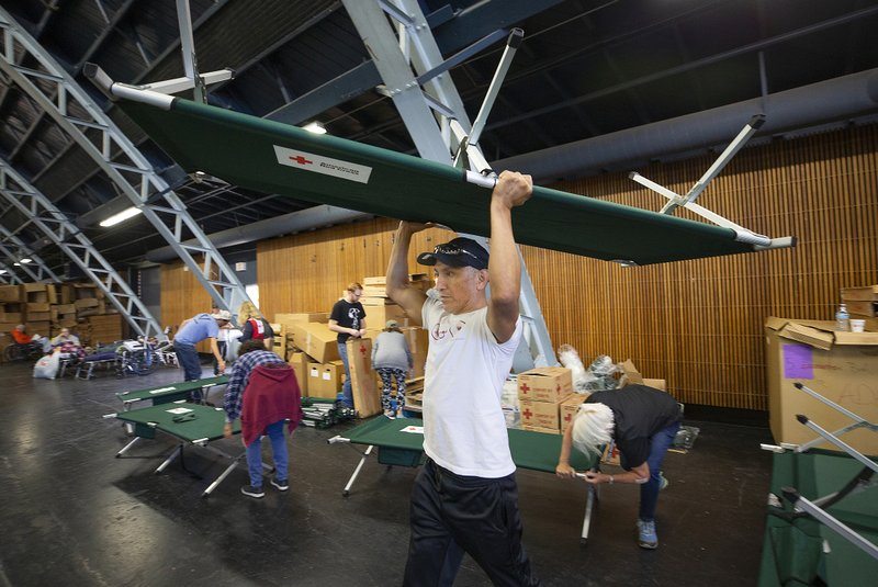 In this Sunday, Oct. 27, 2019, photo, volunteer Alejandro Pablo carries a newly built cot to an evacuee in need at a Red Cross shelter set up for wildfire evacuees at the Sonoma County Fairgrounds in Santa Rosa, Calif. The Red Cross established the shelter for evacuees with or without pets at the Sonoma County Fairgrounds. (John Burgess/The Press Democrat via AP)
