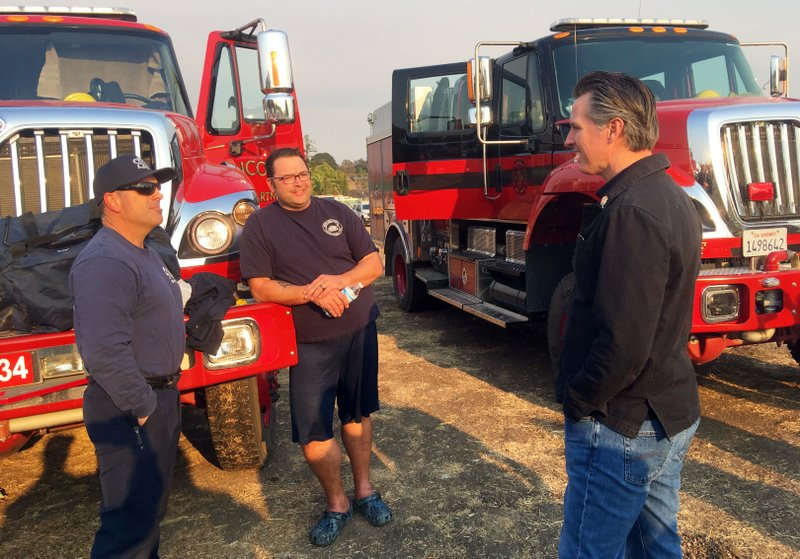 California Gov. Gavin Newsom talks with firefighters Darrin Mayo, left, and Aaron Bjorgum, from Lincoln, Calif., helping fight the Kincade Fire outside Santa Rosa, Calif., Monday, Oct. 28, 2019. (AP Photo Don Thompson)