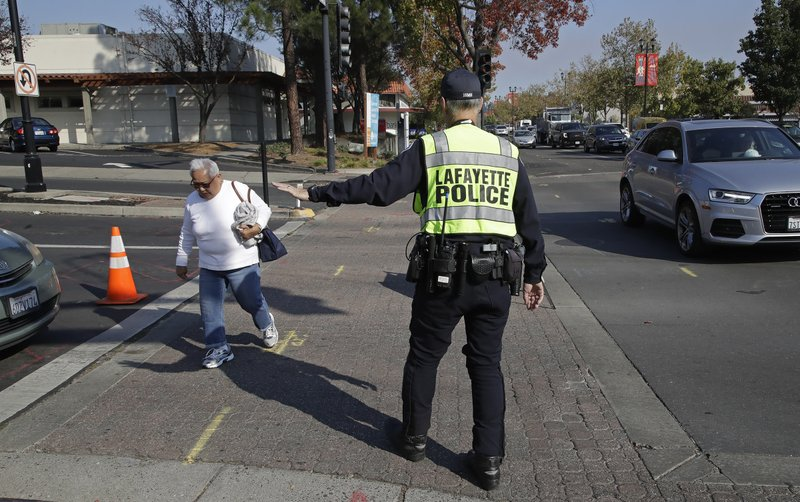 A Lafayette police officer stops traffic for a pedestrian at an intersection that has lost power Monday, Oct. 28, 2019, in Lafayette, Calif. PG&E said Monday its power lines may have started two wildfires over the weekend in the San Francisco Bay Area despite widespread blackouts meant to prevent fires from igniting during dangerously windy weather. (AP Photo/Ben Margot)