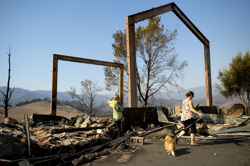 Stephanie LaFranchi, right, and Ashley LaFranchi examine the remains of their family's Oak Ridge Angus ranch, leveled by a wildfire called Kincade Fire, in Calistoga, Calif., on Monday, Oct. 28, 2019. According to Cal Fire, the blaze has scorched more than 66,000 acres and destroyed at least 96 structures. (AP Photo/Noah Berger)
