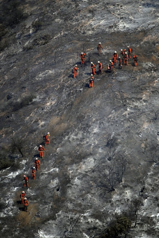 Hand crews walk down a fire-ravaged hillside as the Getty fire burns on Mandeville Canyon Monday, Oct. 28, 2019, in Los Angeles. (AP Photo/Marcio Jose Sanchez)