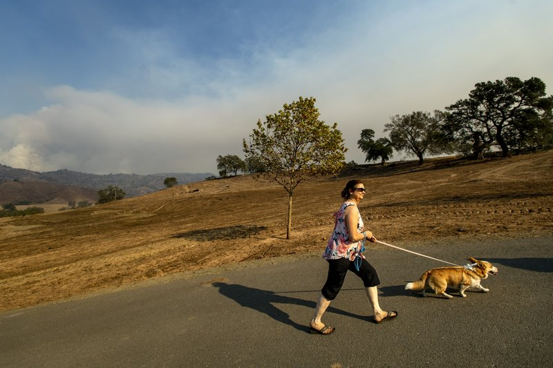 Stephanie LaFranchi climbs a hill to visit the remains of her husband's family home, leveled by the Kincade Fire, in Calistoga, Calif., on Monday, Oct. 28, 2019. According to Cal Fire, the blaze, burning in the background, has scored more than 66,000 acres and destroyed at least 96 structures. (AP Photo/Noah Berger)