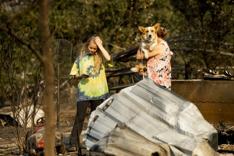 Ashley LaFranchi examines the remains of her family's Oak Ridge Angus ranch, leveled by the Kincade Fire, in Calistoga, Calif., on Monday, Oct. 28, 2019. According to Cal Fire, the blaze has scored more than 66,000 acres and destroyed at least 96 structures. (AP Photo/Noah Berger)