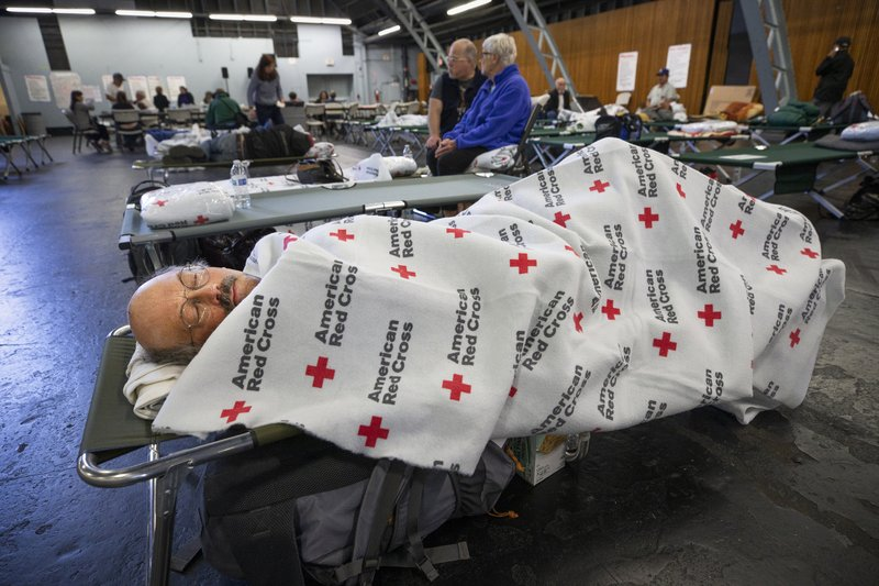 In this Sunday, Oct. 27, 2019, photo, Jim Keefauver rests at a Red Cross shelter set up for wildfire evacuees at the Sonoma County Fairgrounds in Santa Rosa, Calif., after evacuating his Santa Rosa home in the morning. Keefauver said he was sent to the shelter after the Veterans Memorial Building in Santa Rosa reached capacity. (John Burgess/The Press Democrat via AP)