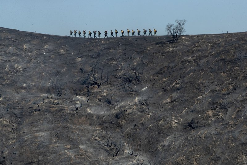 Fire crews walk along a blackened ridge as they battle the Getty fire Monday, Oct. 28, 2019, in Los Angles. (AP Photo/Gregory Bull)