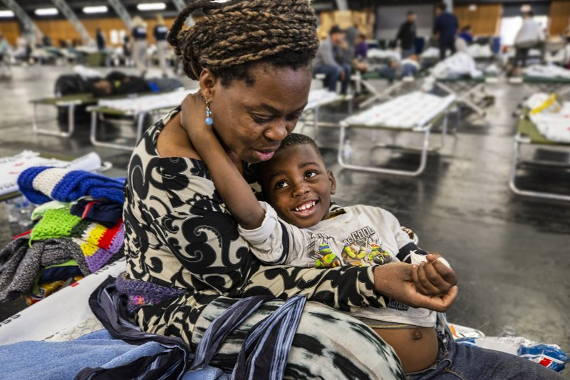 In this Sunday, Oct. 27, 2019, photo, Bernadette Yabadi and her son Victor rest at a Red Cross shelter at the Sonoma County Fairgrounds in Santa Rosa, Calif., after they evacuated their Santa Rosa home, following officials expanded evacuation orders Sunday morning after heavy winds pushed the Kincade Fire to the south. (John Burgess/The Press Democrat via AP)