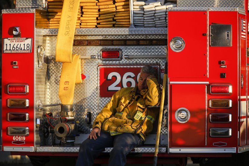 A firefighter leans against his fire truck while resting from working on a wildfire in Los Angeles, Monday, Oct. 28, 2019. (AP Photo/Ringo H.W. Chiu)