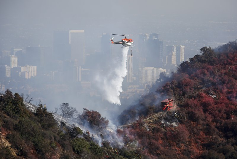 A helicopter drops water as a wildfire called the Getty Fire burns on Kenter Canyon in Los Angeles, Monday, Oct. 28, 2019. (AP Photo/Ringo H.W. Chiu)