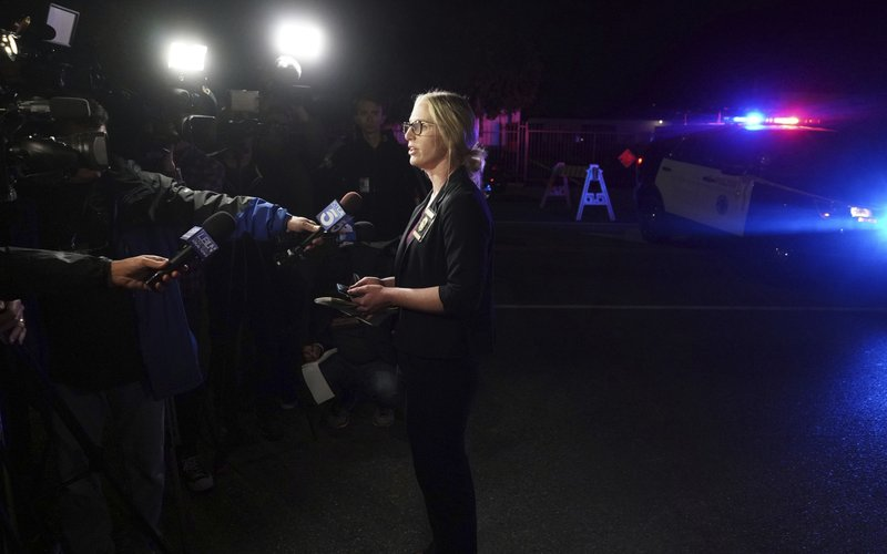 Long Beach Police PIO Jennifer De Prez gives information at the scene of a shooting in Long Beach on Wednesday, Oct. 30, 2019. Authorities say three people were fatally shot and nine others injured at a home in Long Beach, California.(Scott Varley/The Orange County Register via AP)