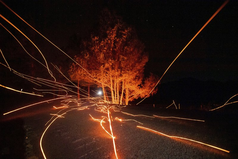 Strong winds send embers flying across Ida Clayton Rd. as the Kincade Fire burns in Calistoga, Calif., on Tuesday, Oct. 29, 2019. Millions of people have been without power for days as fire crews raced to contain two major wind-whipped blazes that have destroyed dozens of homes at both ends of the state: in Sonoma County wine country and in the hills of Los Angeles. (AP Photo/Noah Berger)
