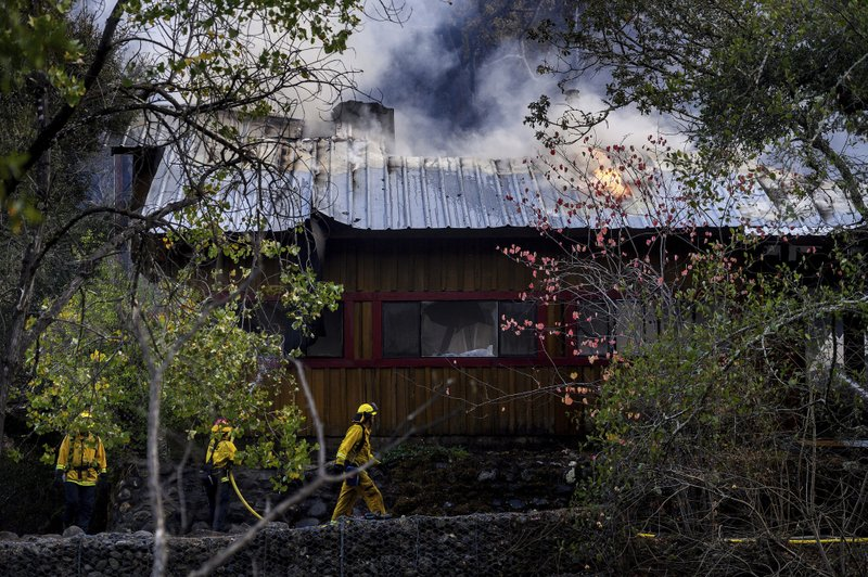 Firefighters pass a burning structure as the Kincade fire burns in Calistoga, Calif., on Tuesday, Oct. 29, 2019.  (AP Photo/Noah Berger)