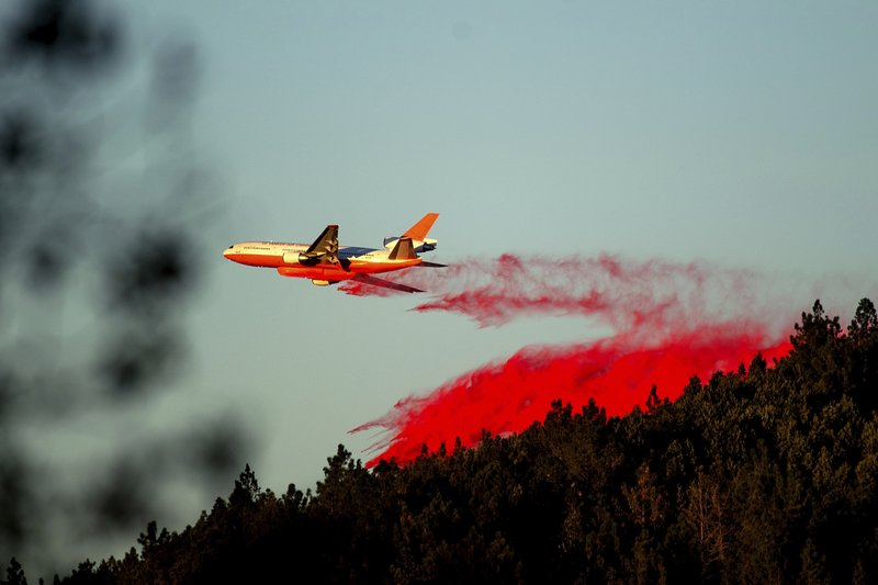 An air tanker drops retardant while battling the Kincade Fire near Healdsburg, Calif., on Tuesday, Oct. 29, 2019. The overall weather picture in northern areas is improving, as powerful, dry winds bring extreme fire weather to Southern California. (AP Photo/Noah Berger)