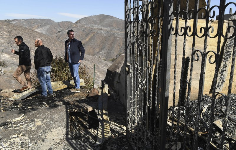 From left, L.A. Mayor Eric Garcetti, L.A. City Councilman Mike Bonin and California Governor Gavin Newsom view a burned and home along Tigertail Road in Brentwood, Calif., Tuesday Oct. 29, 2019. (Wally Skalij/Los Angeles Times via AP, Pool)