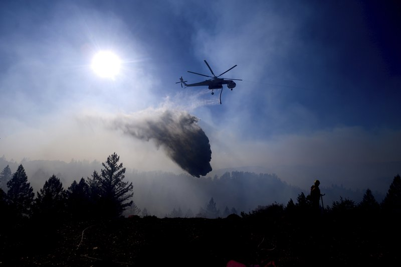 A helicopter drops water while battling the Kincade Fire near Healdsburg, Calif., on Tuesday, Oct. 29, 2019. Millions of people have been without power for days as fire crews race to contain two major wind-whipped blazes that have destroyed dozens of homes at both ends of the state: in Sonoma County wine country and in the hills of Los Angeles. (AP Photo/Noah Berger)