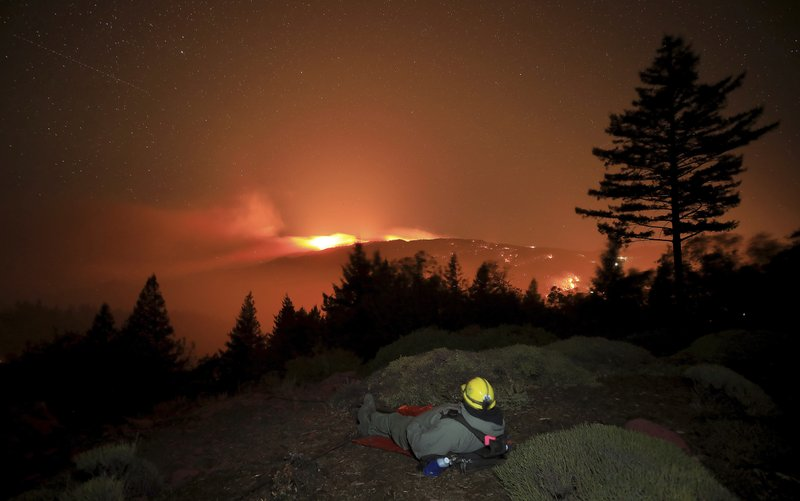 Firefighter Alex DeLeon, of South Lake Tahoe, Calif., bundles up against the cold wind on a ridge between Sonoma and Lake County as the Kincade fire burns, Tuesday, Oct. 29, 2019, in northern California. The flames prompted a flurry of false fire reports on the Santa Rosa plain. (Kent Porter/The Press Democrat via AP)