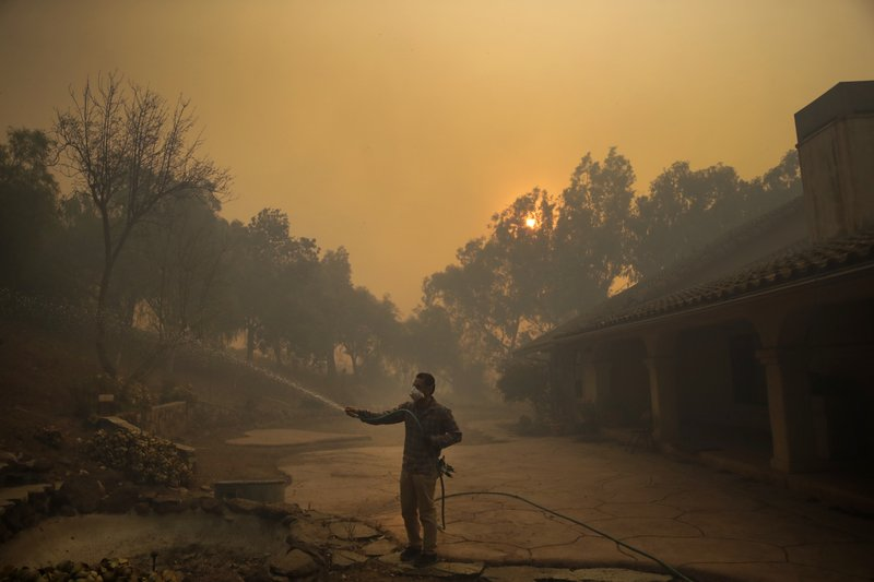 Marco Alcaraz uses a garden hose to protect his girlfriend's home as the Easy fire approaches Wednesday, Oct. 30, 2019, in Simi Valley, Calif.  A new wildfire erupted Wednesday in wind-whipped Southern California, forcing the evacuation of the Ronald Reagan Presidential Library and nearby homes, as both ends of the state struggled with blazes, dangerously gusty weather and deliberate blackouts. (AP Photo/Marcio Jose Sanchez)